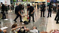 Una mujer se resiste a ser desalojada por los Mossos en la estación de Sants