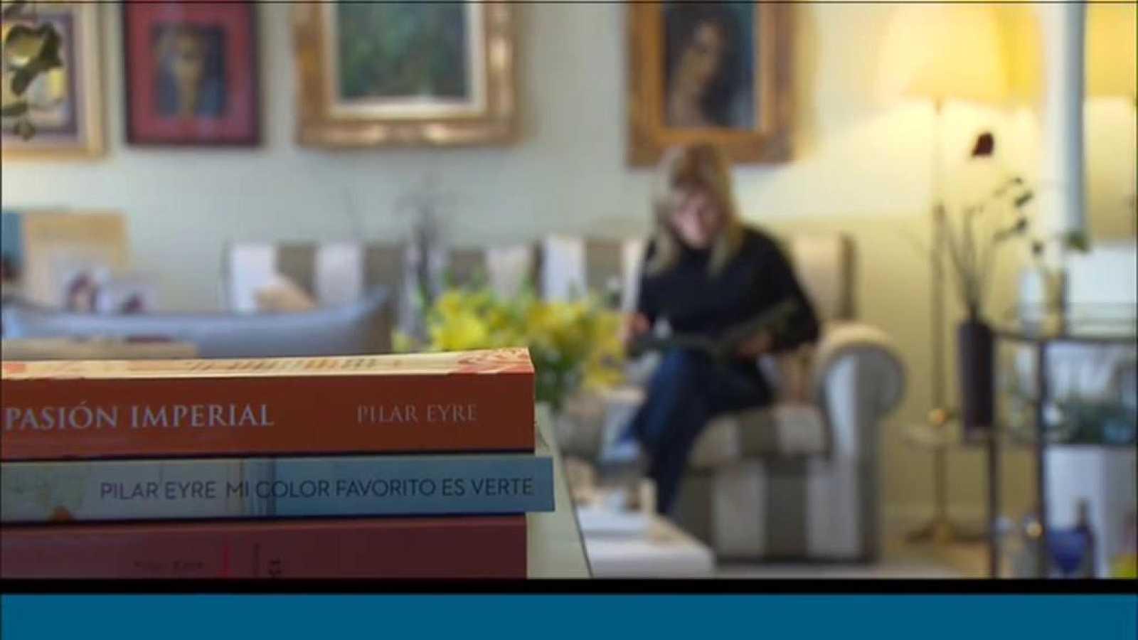 L'escriptora i periodista Pilar Eyre llegint al sofà de casa seva