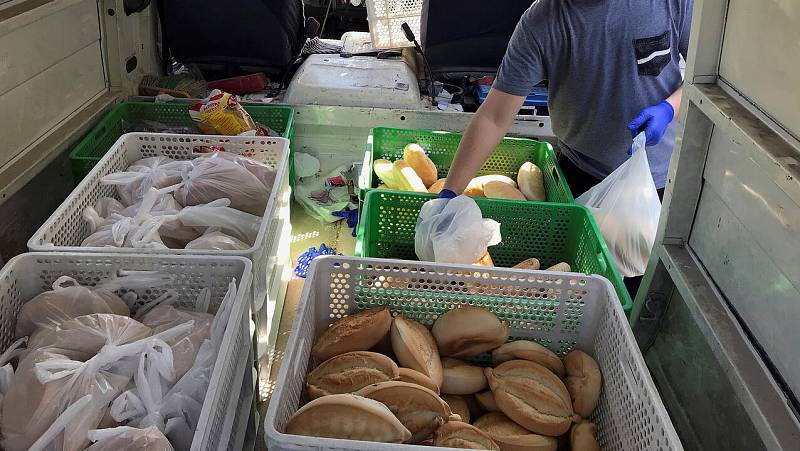 """Voluntarios llevan comida a familias en el barrio sevillano de las """"3.000 viviendas"""" durante el aislamiento"""